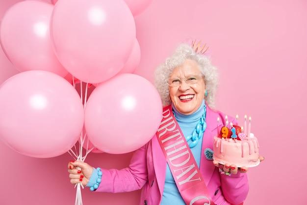 Das leben beginnt erst, wenn man älter wird. frohe faltige alte frau feiert geburtstag hält festlichen kuchen mit brennenden kerzenbündel aufgeblasenen luftballons