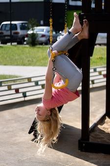Das leben der kinder in einer modernen stadt - das mädchen hat spaß auf dem spielplatz in der nähe des hauses
