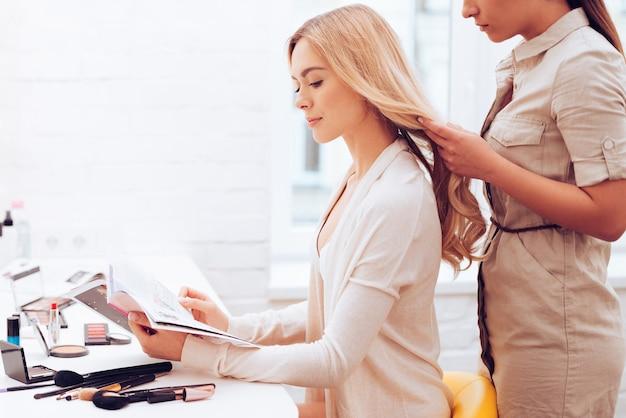 Das leben eines models. seitenansicht einer schönen jungen frau, die eine zeitschrift liest, während die friseurin ihr haar im make-up-raum anpasst
