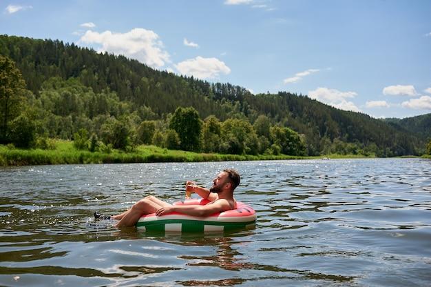 Das leben genießen. junger mann, der mit einem glas bier auf dem fluss ruht. entspannung, urlaub, lifestyle-konzept
