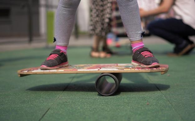 Das leben in einer modernen stadt - ein mädchen reitet ein balanceboard auf einem fortgeschrittenen spielplatz