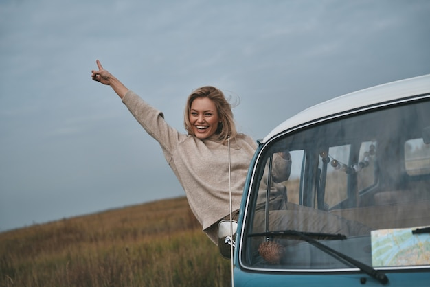 Das leben ist großartig! attraktive junge lächelnde frau, die sich aus dem fenster des vans lehnt und gestikuliert, während sie die autofahrt genießt