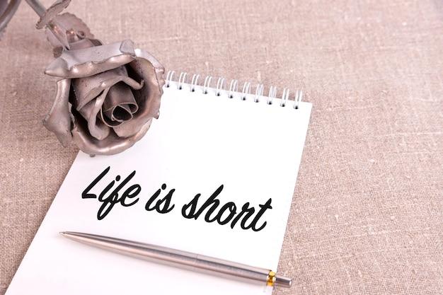 Das leben ist kurz, der text ist in ein notizbuch geschrieben, das auf leinen und einer eisernen rosenblume liegt.