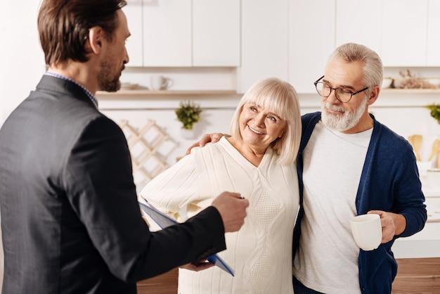 Das leben unserer älteren generation verbessern. kompetenter, intelligenter und hilfreicher rechtsberater, der den alten kundenpaaren einen vertrag vorlegt und vorstellt und gleichzeitig vertrauen zum ausdruck bringt