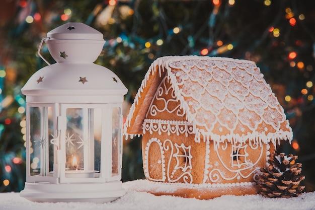 Das lebkuchenhaus über defokussierten lichtern von chrismtas baum