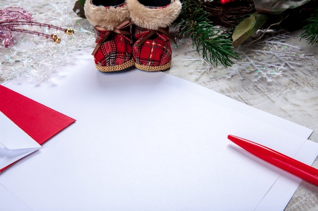 Das leere blatt papier auf dem holztisch mit einem stift und weihnachtsschmuck.
