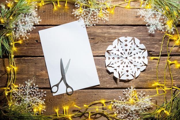 Das leere blatt papier auf dem holztisch mit einer schere und weihnachtsschmuck.