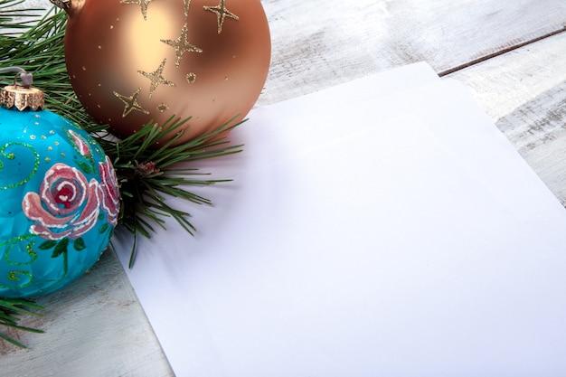 Das leere blatt papier auf dem holztisch mit weihnachtsschmuck.