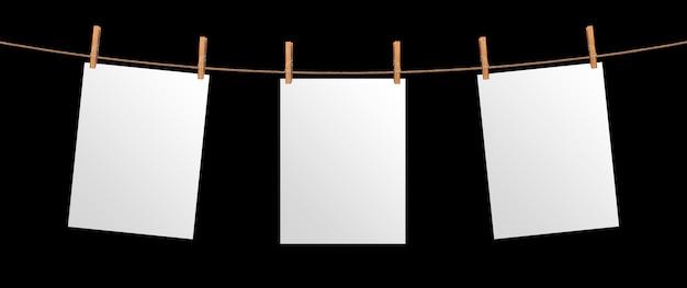 Das leere papierblatt, das am seil, lokalisiert auf schwarzem hintergrund hängt, verspotten oben für ihr projekt, plakatschablone