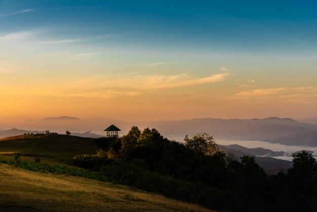 Das licht der abendsonne scheint auf den hohen berg und den dichten weißen nebel.
