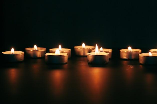 Das licht der kerze beleuchtet die dunkelheit