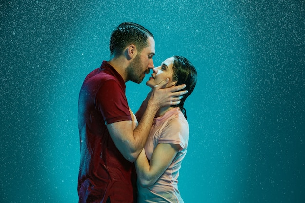 Das liebende paar, das im regen auf einem türkisfarbenen hintergrund küsst
