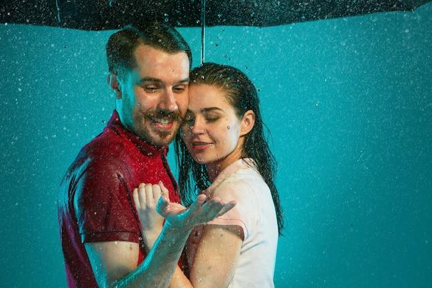 Das liebende paar im regen mit regenschirm auf einem türkisfarbenen hintergrund