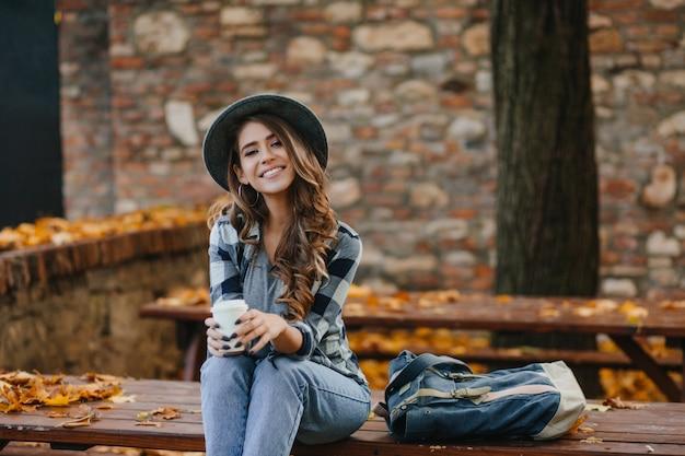 Das liebenswerte europäische weibliche model trägt lässige jeans und ein blaues hemd, die im warmen oktoberwochenende draußen sitzen