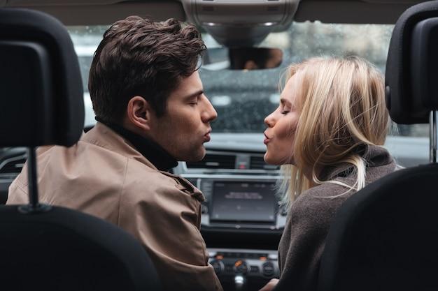 Das liebevolle paar, das im auto küsst mit augen sitzt, schloss.