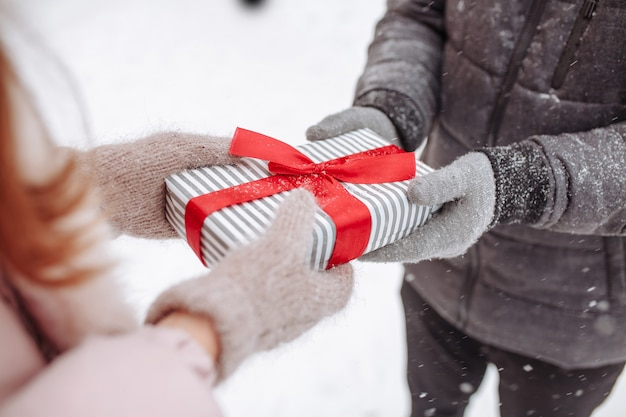 Das liebevolle paar schenkt sich im schneebedeckten winterpark draußen wollhandschuhe. gestreifte box mit roter schleife in den händen eines mannes und einer frau. valentinstag konzept. frauentag.