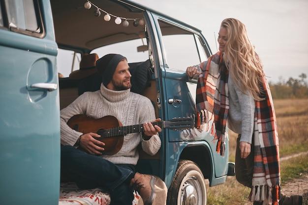 Das lied der liebe hören. hübscher junger mann, der gitarre für seine schöne freundin spielt, während er im blauen retro-stil-minivan sitzt