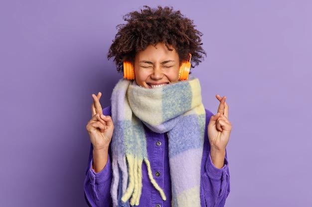 Das lockige ethnische mädchen drückt die daumen und glaubt an das glück, hört ein angenehmes lied in kopfhörern und trägt einen warmen winterschal.