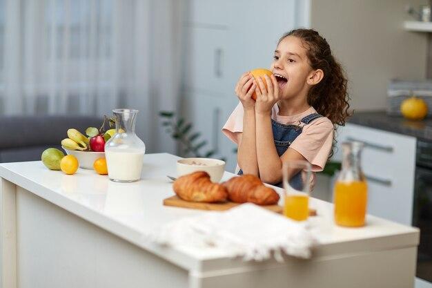 Das lustige kleine mädchen mit dem lockigen haar frühstückt zusammen mit der mutter in der küche, versucht, eine frucht zu essen.