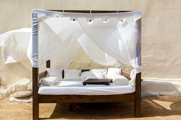 Das luxuriöse moderne bett in weißer farbe mit baldachin zum entspannen. der wind zerzaust das weiße baldachin.