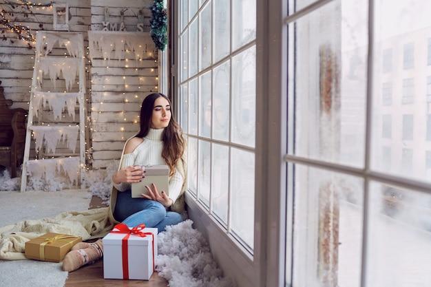 Das mädchen am fenster mit geschenken im winter