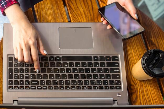 Das mädchen arbeitet hinter einem laptop an einem tisch in einem café neben einem tasse kaffee