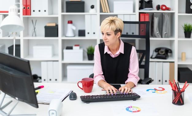 Das mädchen arbeitet im büro am computer.