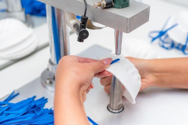 Das mädchen arbeitet in einer fabrik für die herstellung von medizinischen masken mit nanofaser und lötschleifen mit ultraschall auf einer maschine.