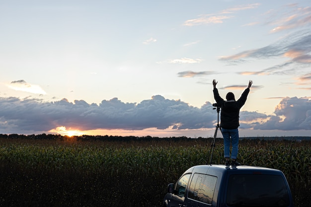 Das mädchen auf dem dach des autos fotografiert den sonnenuntergang mit einem stativ.