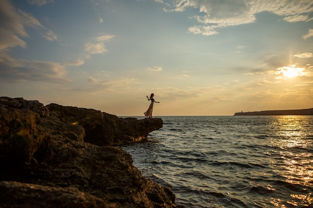 Das mädchen auf dem hintergrund eines schönen meerblicks und des sonnenuntergangs, schattenbild eines mädchens auf einer klippe, auf einer klippe, einem schönen himmel und einem meer