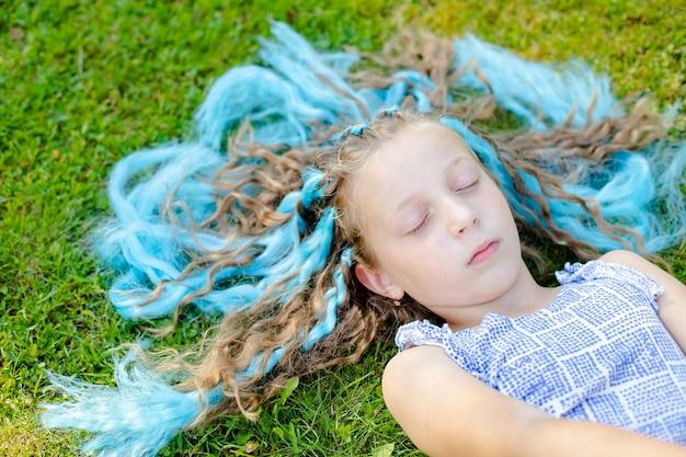 Das mädchen auf dem rasen. ruhe in der natur. auf der wiese schlafen, träumen. das gras streicheln