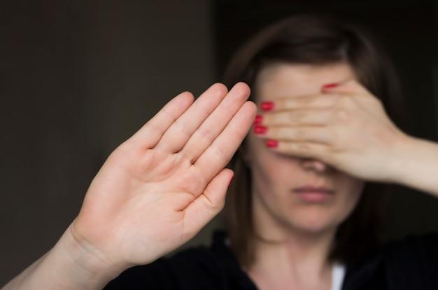 Das mädchen bedeckte ihr gesicht mit der hand und streckte die hand nach vorne