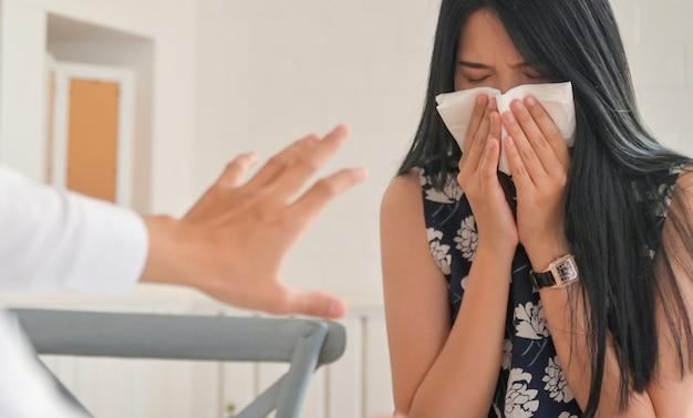 Das mädchen bedeckte ihr gesicht mit einem taschentuch, das mit leuten nieste, die ihre hände hoben, verbieten.