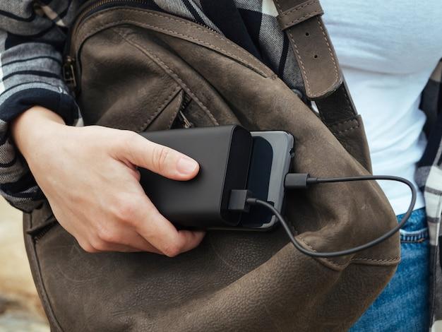 Das mädchen benutzt ein smartphone, das an die power bank angeschlossen ist