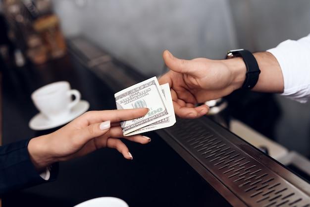 Das mädchen bezahlt den barmann für die bestellung.