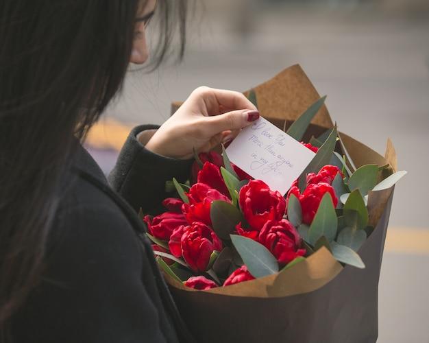 Das mädchen, das eine anmerkung liest, setzte sich in einen blumenstrauß der roten tulpen