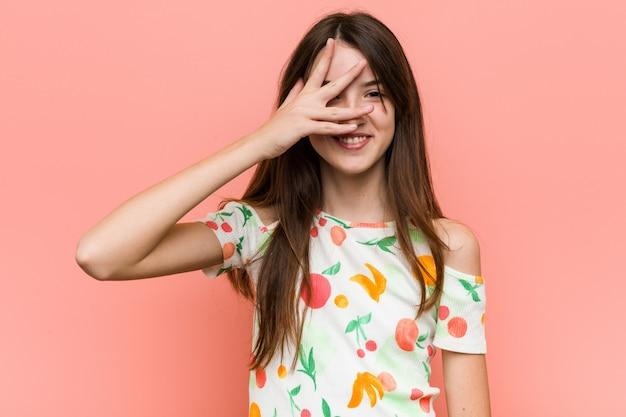Das mädchen, das einen sommer trägt, kleidet gegen ein wandblinzeln durch finger, verlegenes bedeckungsgesicht.
