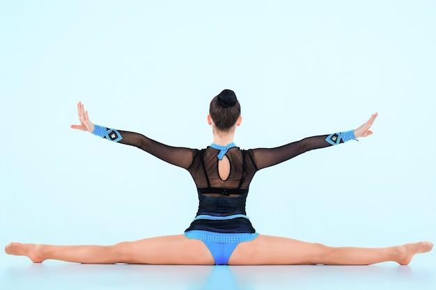 Das mädchen, das gymnastik macht, tanzt auf einem blauen raum