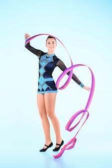 Das mädchen, das gymnastik tanzt, tanzt mit farbigem band auf einem blauen hintergrund