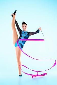 Das mädchen, das gymnastik tut, tanzen mit farbigem band auf einer blauen wand