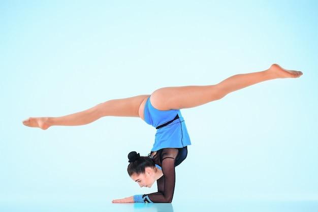 Das mädchen, das gymnastik tut, tanzt auf einem blauen hintergrund
