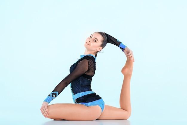 Das mädchen, das gymnastik tut, tanzt auf einer blauen wand