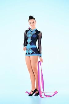 Das mädchen, das gymnastik tut, tanzt mit farbigem band an einer blauen wand