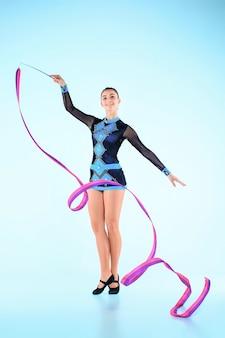 Das mädchen, das gymnastik tut, tanzt mit farbigem band auf einem blauen raum
