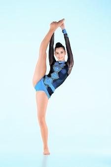 Das mädchen, das gymnastiktanz auf einer blauen wand tut