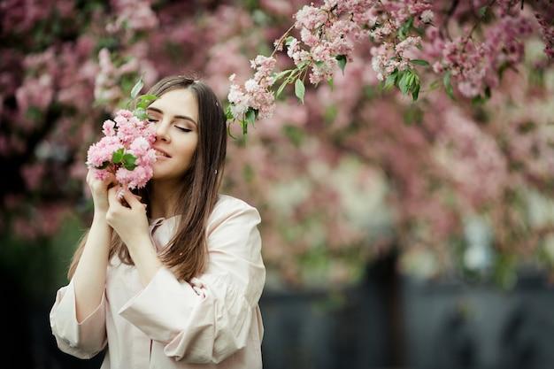 Das mädchen, das ihre augen schließt, lächelt und hält einen kirschblüte-zweig
