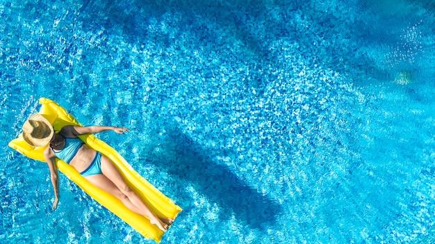 Das mädchen, das im swimmingpool sich entspannt, kind schwimmt auf aufblasbarer matratze und hat spaß im wasser auf familienurlaub, tropischer ferienort, luftbrummenansicht von oben