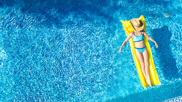 Das mädchen, das im swimmingpool sich entspannt, kind schwimmt auf aufblasbarer matratze und hat spaß im wasser auf familienurlaub