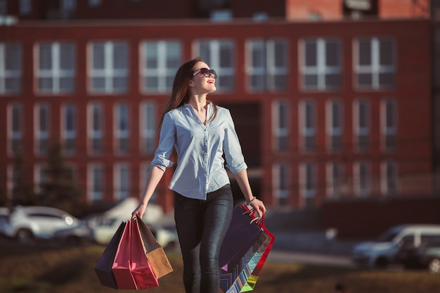 Das mädchen, das mit dem einkaufen auf stadtstraßen geht