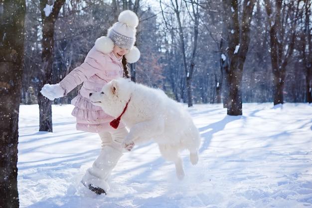 Das mädchen, das mit einem samoyedwelpen in einem schnee spielt, bedeckte park am weihnachtsmorgen